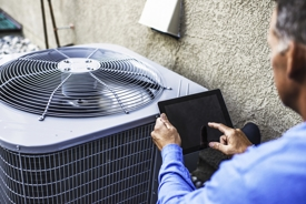 HVAC technician using iPad in front of a new air conditioner.